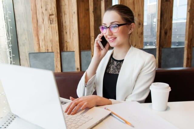パソコンを見ながら笑顔で電話対応をするフェミニンな雰囲気の女性