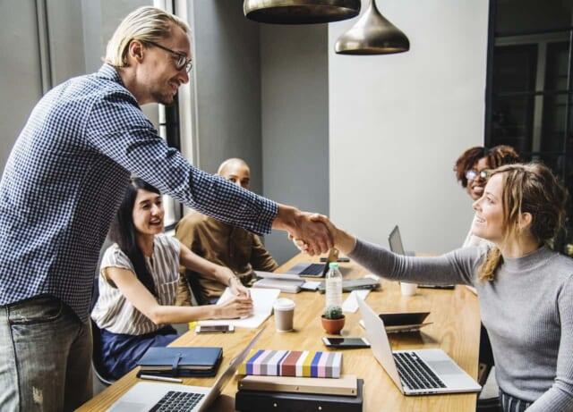 上司とフレンドリーな笑顔で握手を交わす女性