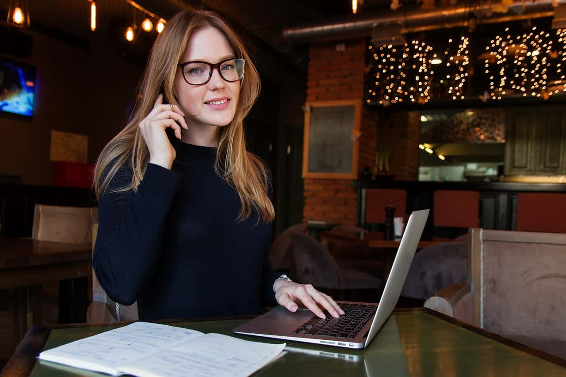 仕事をしながらこちらを見て微笑むかわいらしい雰囲気の女性