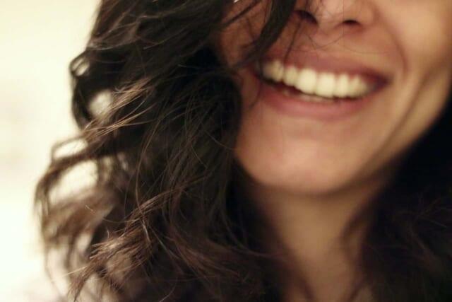 まっ白な歯にしっかりと上がった口角が印象的な女性の笑顔