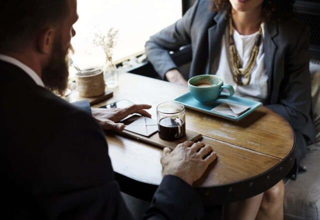 カフェでコーヒーを飲みながら話をする職場の先輩と後輩