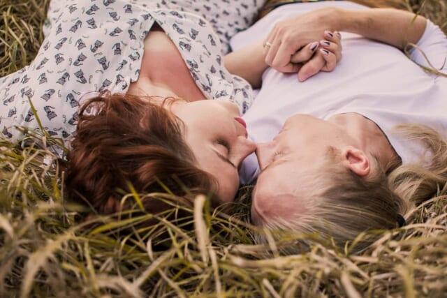 草むらに寝転がって見つめあう幸せそうなカップル