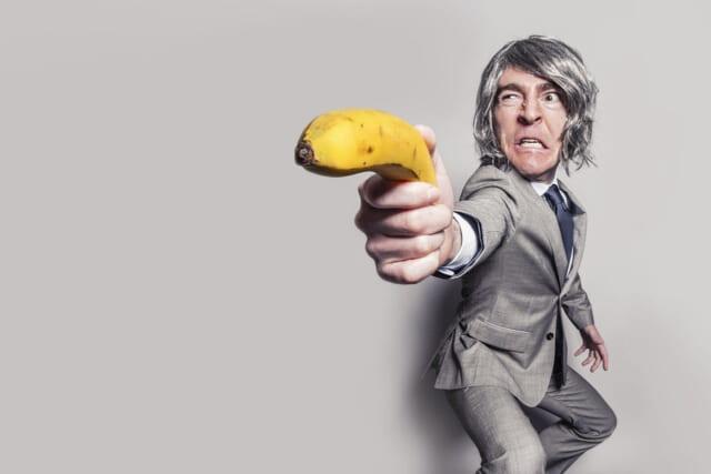 バナナをピストルのように突き出すモテないオタク風の男性