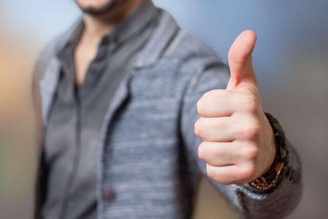 親指を立てて相手の意見を快く尊重する男性