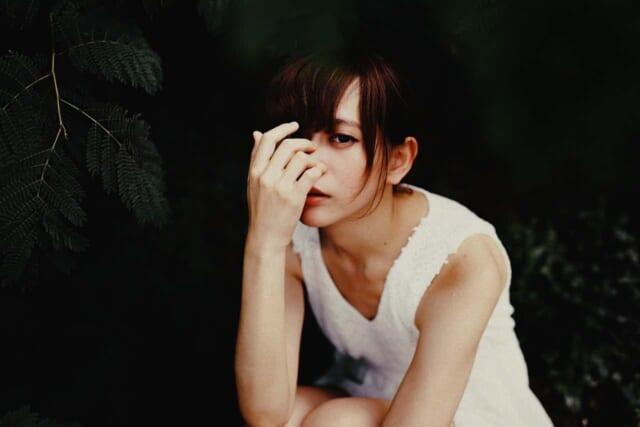 性格は暗そうで、不健康なほど真っ白い肌なのにかわいらしい雰囲気を漂わせる白いワンピースを着た女性女性