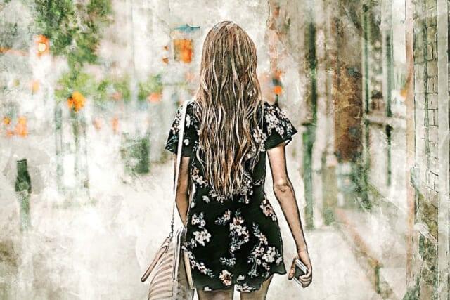 街中を歩く黒い花柄のミニワンピースにショルダーバッグをかけたロングヘアーの女の子の後ろ姿