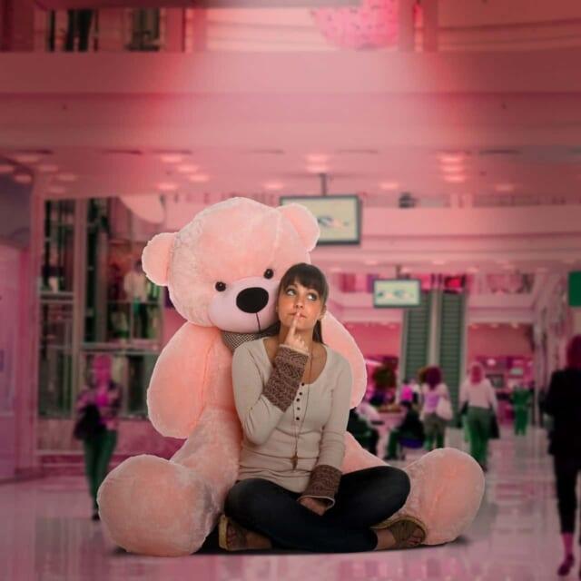 自分よりも大きなピンク色のクマのぬいぐるみに寄りかかる前髪パッツンの女の子