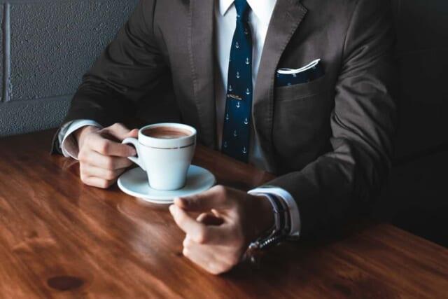 カフェでくつろぐスーツを着た清潔感たっぷりな男性
