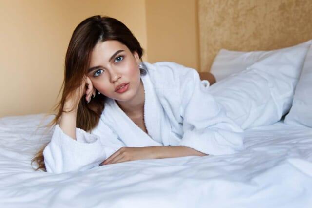 白いバスローブを着てベッドに寝そべり可愛らしい瞳を向ける女の子