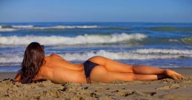 旅先で開放的になりトップレスで砂浜で寝転ぶ女の子