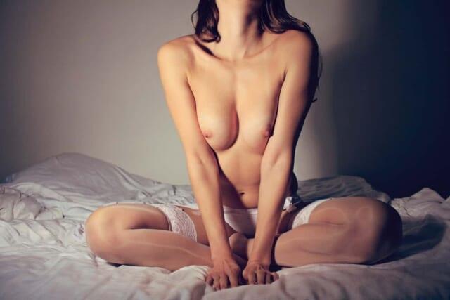 ガーターベルトとストッキングを身に付けてベッドの上に座る女の子