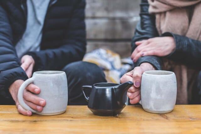 カフェでコーヒーを飲みながら話をするカップル