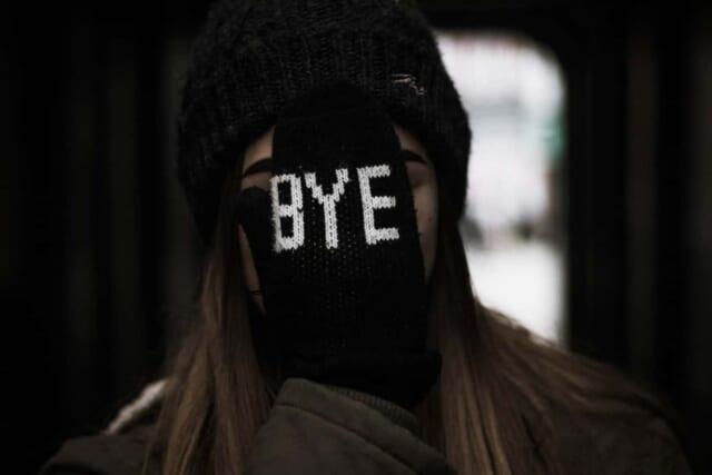 """""""BYE""""と書かれたミトンで顔を隠す女の子"""