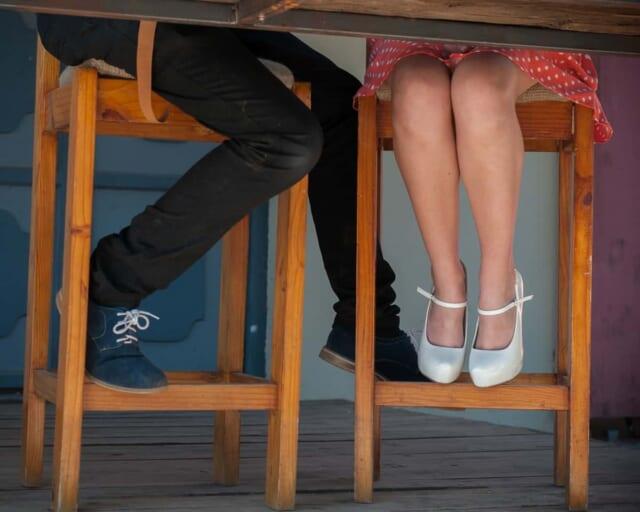 カフェのテーブル席に座りながら女の子を口説く男性の足元