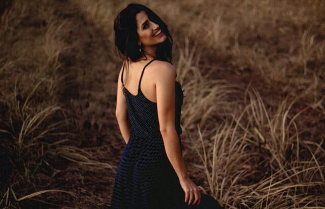 黒い髪をなびかせ草むらの中を歩きながら振り向く雰囲気美人