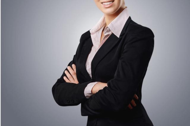 抜群のスタイルでビジネススーツをパリッと着て微笑む経済面でも精神面でも自立していそうな女性