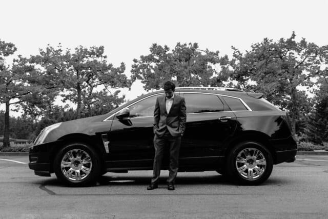 シワひとつないスーツを着て黒い車の前に立つハイスペック男子