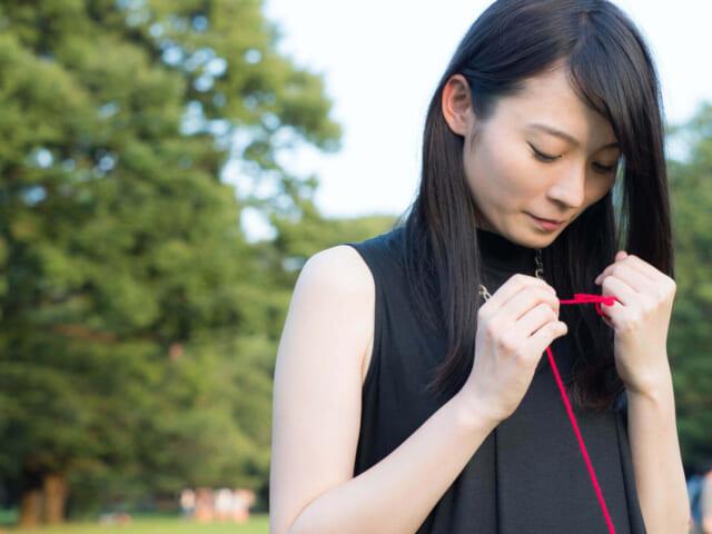 赤い糸を見つめる女性
