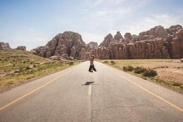大きな道路の中央でジャンプしている女性
