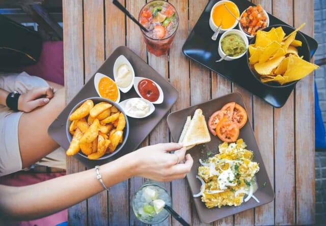 デートで食事をするカップルの前のテーブルに並ぶ沢山の料理