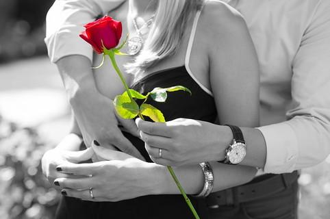 女性に真っ赤なバラを女性に渡し甘える男性