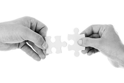 お互いに合わせようとしている違う形のパズルのピースを持った男女