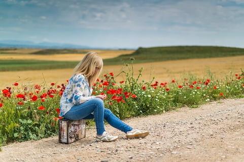 彼氏と喧嘩をしてひとり家を飛び出し旅行鞄ひとつ持ち路上に座り込む女性