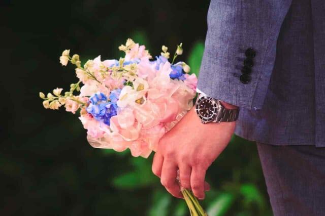 気になる女性にアプローチしようとバラの花を背中の後ろに隠す男性
