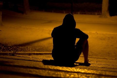 夕暮れの薄暗い公園で女性からの返事がなかったと膝を抱えて落ち込む男性