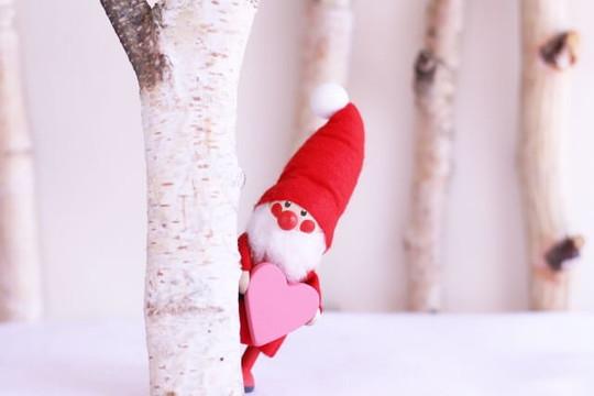木の影から覗くハート型のプレゼントを持ったサンタクロースの人形