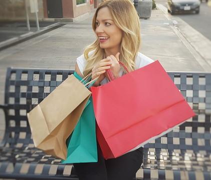 ショッピングバッグをもって嬉しそうにしている女性
