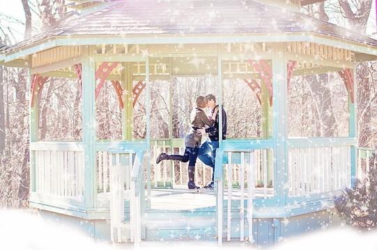 雪の降る中ガゼボでキスをするカップル