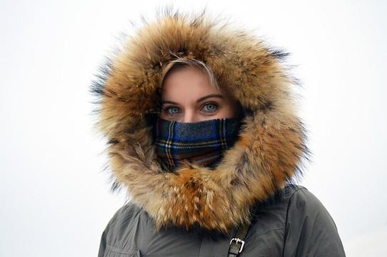 マフラーでマスクをしてフードをすっぽり被って顔も良く見えないほど防寒している女性