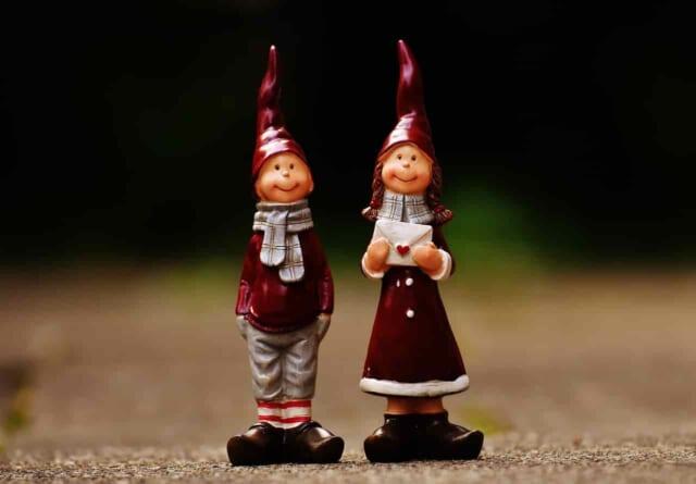 ペアのクリスマスの帽子を被った男女の人形