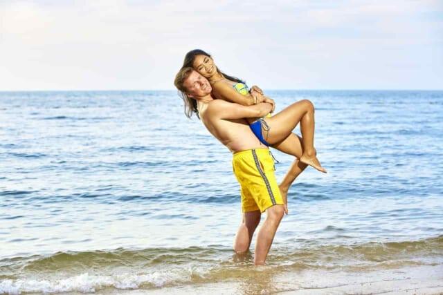 ビーチで楽しそうにしている水着のカップル