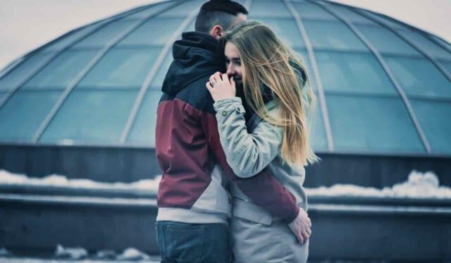 雪の積もる寒そうな中ハグするカップル