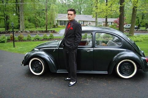 自慢げに自分の車の前に立つお金持ちでプライドの高そうなスーツの男性