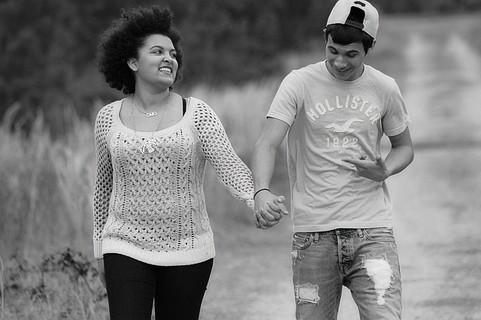 楽しそうに手をつないで会話をしながら歩くカップル