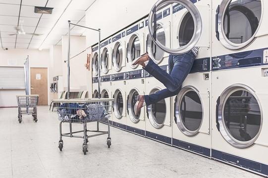 洗濯機の中に上半身入れて覗いている女性