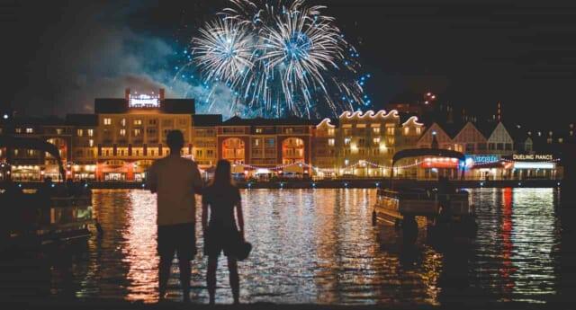 川越しに新年を祝う花火の上がっている派手な夜景を見ているカップル