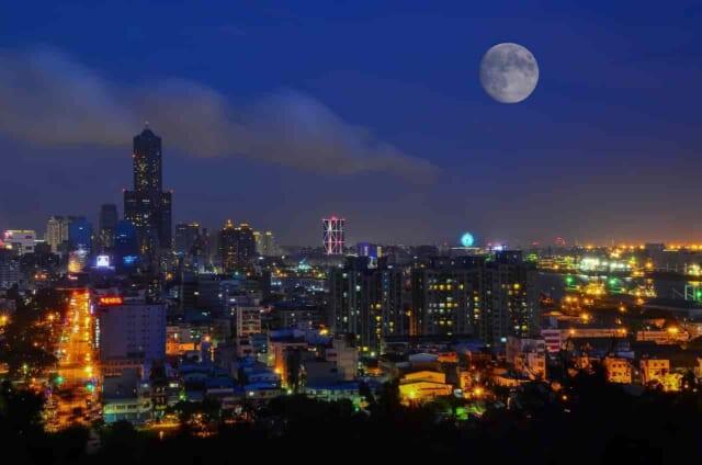 カップルで車から眺める満月の浮かぶ鮮やかなライトの灯る大晦日の夜景
