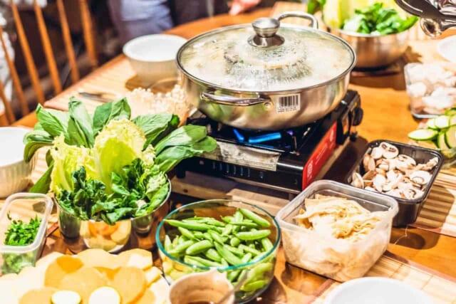 大晦日にお鍋を一緒に調理して楽しんでいるカップル