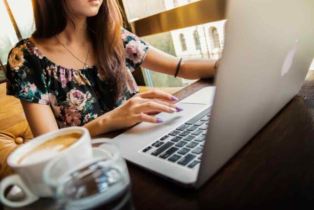 パソコンとスマホを駆使して相手の事をネットで調べている女性