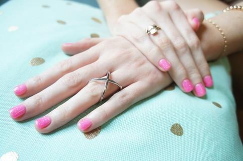 ピンクで柔らかく女性らしいネイルをした女性の指先
