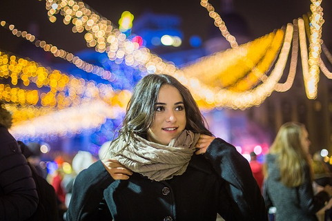寒そうな冬の夜でも女性らしさを忘れず可愛い服装に可愛い髪形で出かける女子力の高い笑顔の魅力的な女性