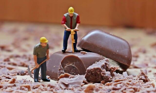 あまりにも大きすぎるチョコレートを貰ってしまい鶴嘴で小さく解体しながら食べようとしている困惑気味な男性