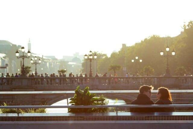 幸せそうにベンチに座りながら話をしているカップル