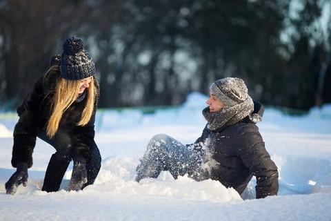 積もった雪の中で転がりながらも楽しそうに遊んでいるカップル