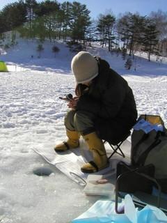 湖の氷に穴をあけ氷上でワカサギ釣りをする女性