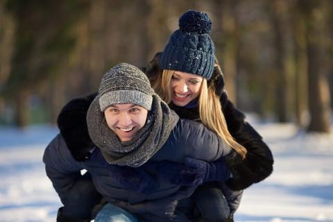 雪の中で彼女をおんぶして楽しそうに走り回る男性